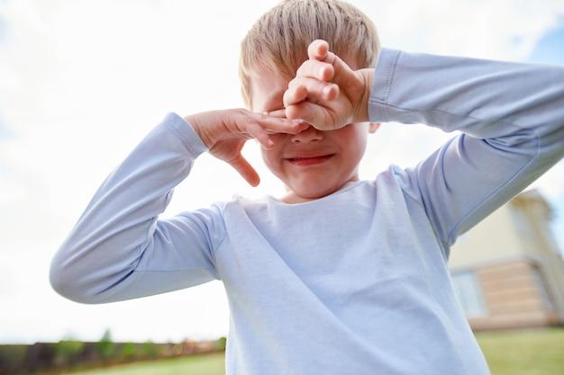 Плачущий маленький мальчик на детской площадке