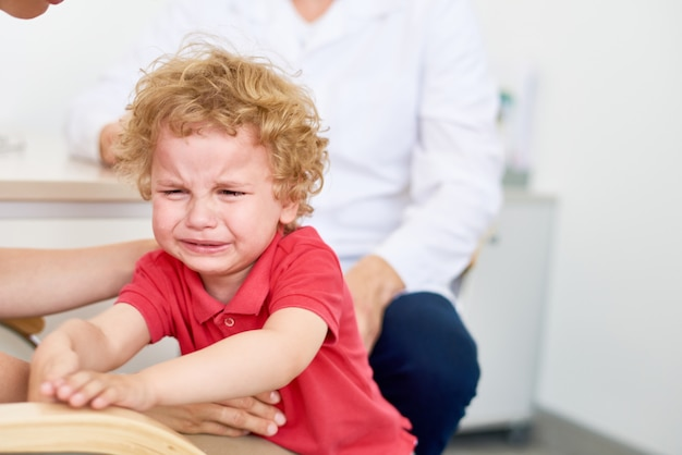 Crying little boy at pediatrician office