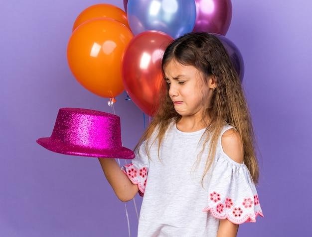 Piangendo piccola ragazza caucasica con cappello da festa viola in piedi di fronte a palloncini di elio isolati su parete viola con spazio di copia purple