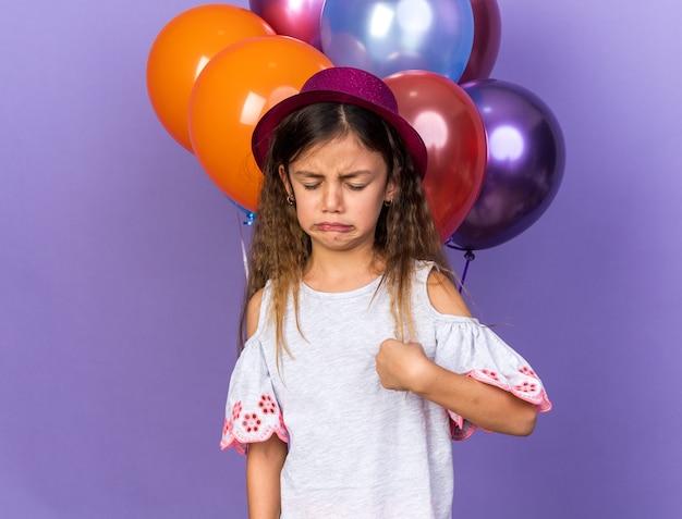 Piangendo piccola ragazza caucasica con cappello da festa viola in piedi di fronte a palloncini di elio isolati su parete viola con spazio di copia