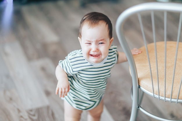 Crying little cutie drk-haired girl, stands crying loudly, standing near chair at home