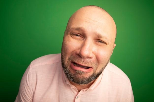 Piangere guardando dritto uomo calvo di mezza età che indossa la maglietta rosa isolata sul verde