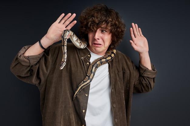 Плачущий самец боится змеи, которая обвивается вокруг его шеи, стоит и кричит изолированно на черной стене