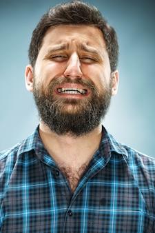 Crying man in blue shirt