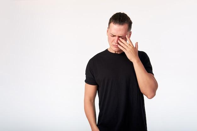 스튜디오에서 검은 면화 반팔 티셔츠를 입고 우는 남자. 스튜디오는 흰색 배경에 촬영.