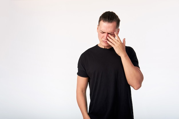 Crying man wearing a black cotton short-sleeved t-shirt in studio. studio shot on a white background.
