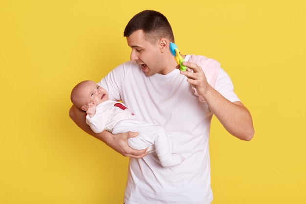 Crying newborn baby on father's hands, handsome young male holding toy in hand and showing toy for his infant, posing isolated over yellow wall, male wearing white t shirt.