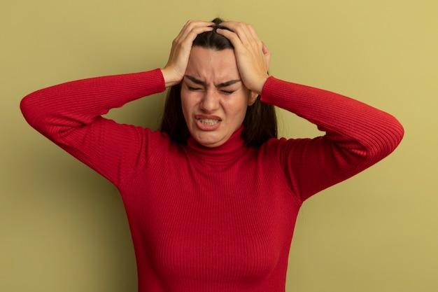 Плачет довольно кавказская женщина, положив руки на голову на оливково-зеленом