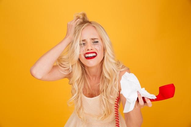 Плачет кричать молодая блондинка разговаривает по телефону.