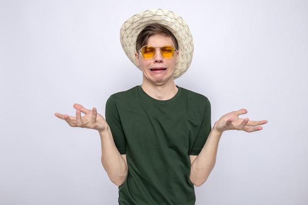 Piangere allargando le mani giovane bel ragazzo con gli occhiali con il cappello