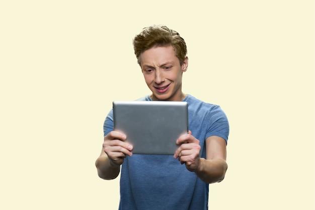 우는 십대 소년이 태블릿을 보고 있다