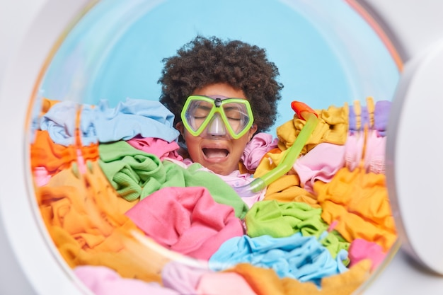 Crying tired woman with afro hair feels very upset after doing housework drowned in pile ofdirty laundry poses in washing machine wears snorkeling glasses on eyes blue wall