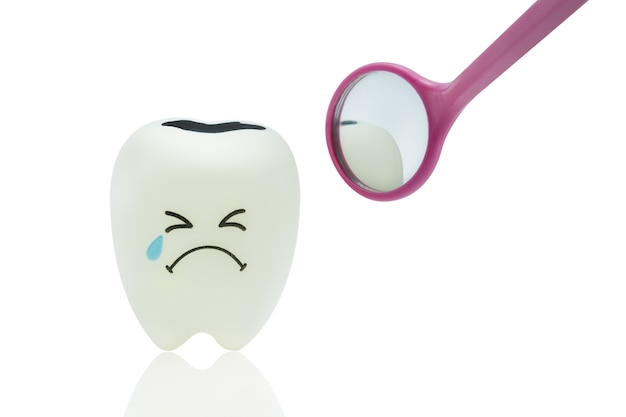 Crying tooth toy emotion with dental mirror on white background