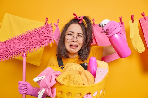 Crying upset young asian woman wears round spectacles holds spray detergent and mop stands near laundry basket frustrated to have much housework