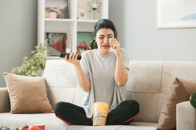 Piangere asciugandosi gli occhi con il tovagliolo ragazza con il telecomando della tv seduto sul divano dietro il tavolino nel soggiorno