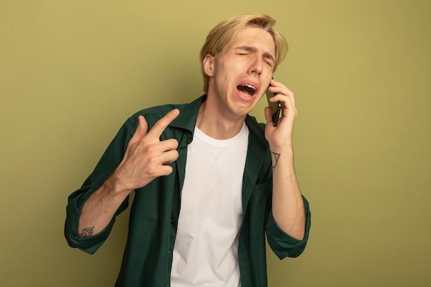Piangendo con gli occhi chiusi il giovane ragazzo biondo che indossa la maglietta verde parla sul telefono