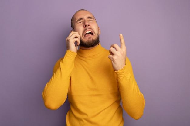 目を閉じて泣いている若いハンサムな男は、紫色で隔離されたアップで電話ポイントで話します