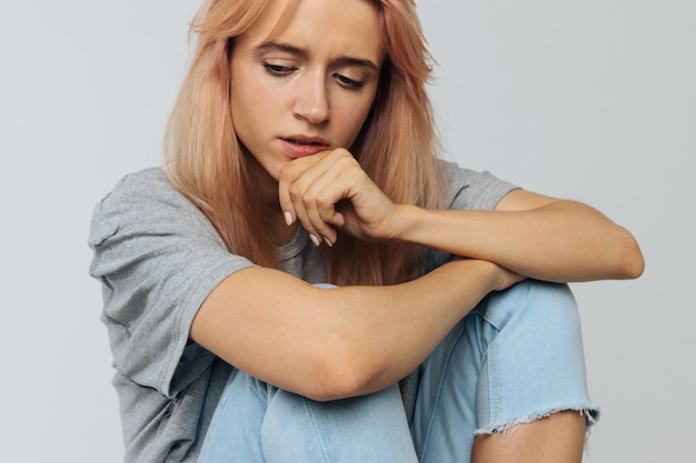 Crying woman in depression looking down, touching her chin, thinking. relationships, love depression