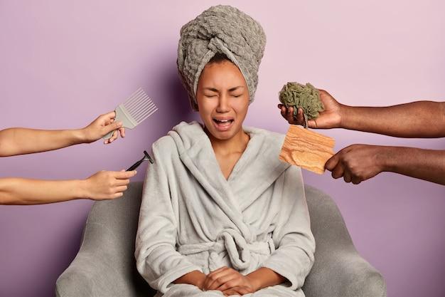 La donna che piange ha l'espressione del viso frustrata, si siede in accappatoio, stanca delle procedure di bellezza