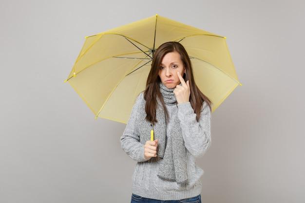 Плачущая женщина в сером свитере, шарфе с желтым зонтиком, держащим указательный палец на щеке, изолированном на сером фоне. здоровый образ жизни моды, концепция холодного сезона эмоций людей. копируйте пространство для копирования.