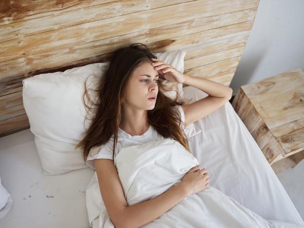 침대 불만족 건강 문제에 누워 우는 여자