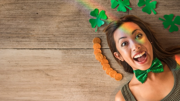 Crying woman near heap of coins and paper clovers on floor