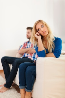Плачущая женщина, сидящая со своим парнем на заднем плане