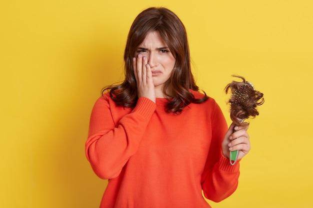 Плачущая женщина страдает от выпадения волос