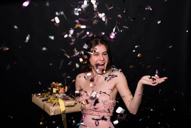 Crying woman with present boxes between confetti