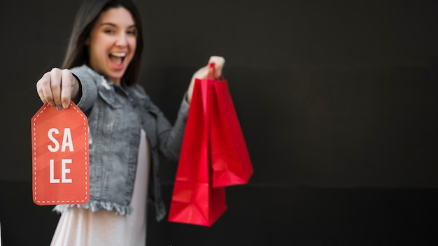 Crying woman with shopping packets and sale tablet