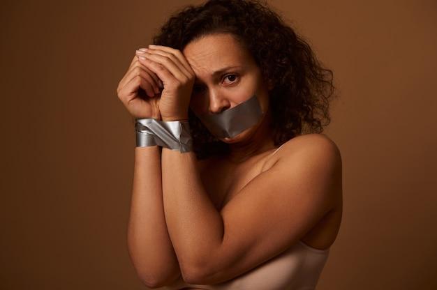 손을 묶고 입을 막고 눈물을 흘리며 우는 여성, 복사공간이 있는 어두운 배경에 고립된 절망감으로 카메라를 바라보고 있습니다. 여성에 대한 제거 폭력의 개념