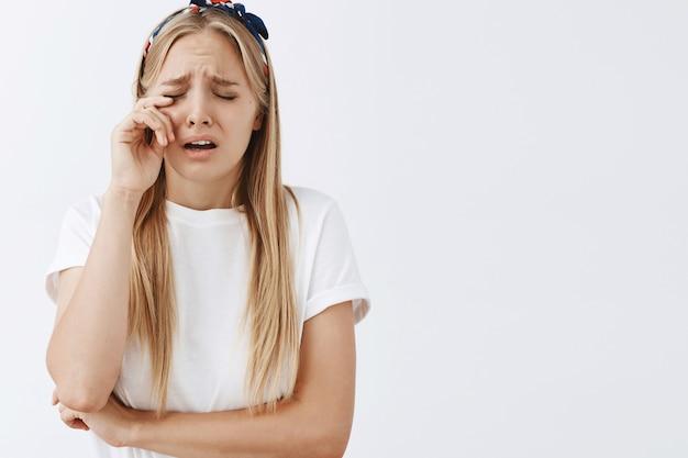 白い壁に向かってポーズをとって泣いている若いブロンドの女の子