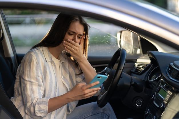 우는 어린 소녀는 휴대전화로 메시지를 읽었으며 차의 운전석에서 좌절한 젊은 여성을 좌절시켰다