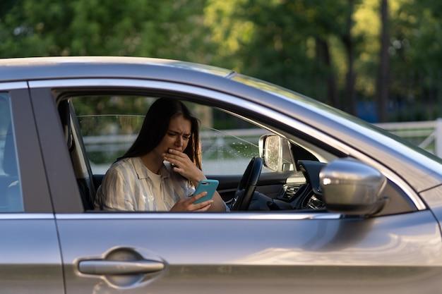 우는 어린 소녀가 휴대전화로 메시지를 읽고 차 운전석에서 화가 난 젊은 여성을 좌절시켰다