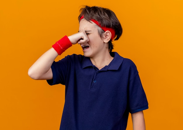 Crying young handsome sporty boy wearing headband and wristbands with dental braces wiping tears isolated on orange wall