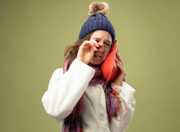白いローブとスカーフと冬の帽子を身に着けている泣いている若い病気の女の子は、オリーブグリーンで隔離の手で頬拭き目に湯たんぽを置きます