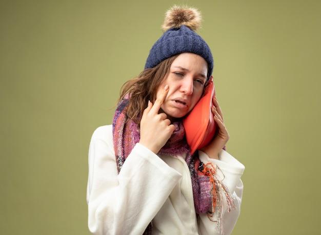 Piangere giovane ragazza malata che indossa una veste bianca e cappello invernale con sciarpa mettendo la borsa dell'acqua calda sulla guancia tenendo il dito sulla guancia isolato su verde oliva