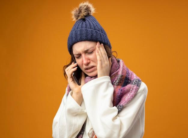 Piangere la giovane ragazza malata che indossa la veste bianca e il cappello invernale con la sciarpa parla al telefono mettendo la mano sul tempio isolato sull'arancio
