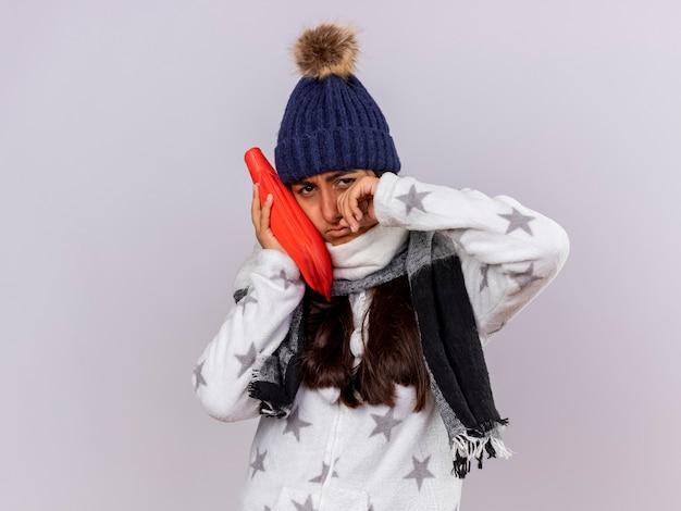 Piangere giovane ragazza malata che indossa cappello invernale con sciarpa che mette la borsa dell'acqua calda sulla guancia e asciugandosi gli occhi