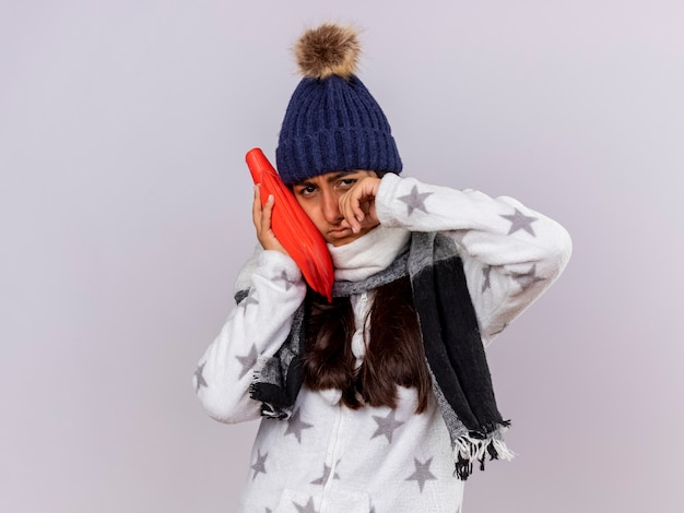 頬に湯たんぽを置き、目を拭くスカーフと冬の帽子をかぶって泣いている若い病気の女の子