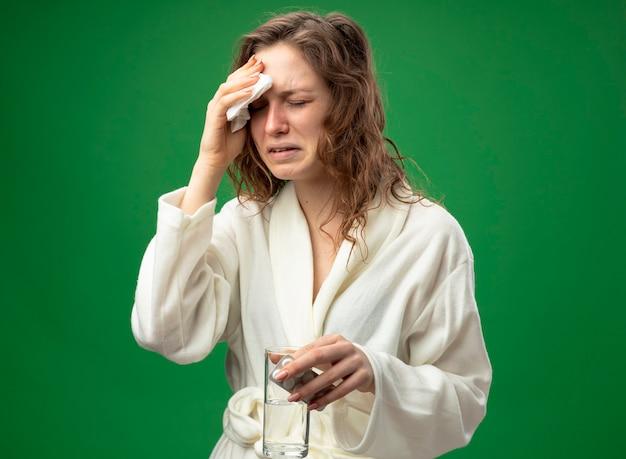 Плачущая молодая больная девушка с закрытыми глазами в белом халате, держащая стакан воды с таблетками и вытирающая лоб салфеткой, изолированной на зеленом