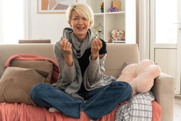 Piangendo giovane donna slava malata con una sciarpa intorno al collo che tiene in mano una siringa e una fiala medica seduta sul divano in soggiorno