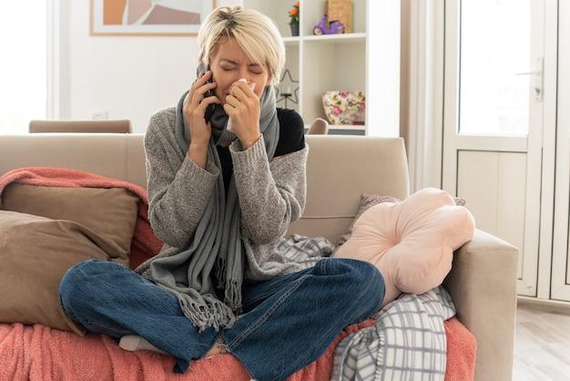 목에 스카프를 두른 우는 젊은 슬라브 여성은 거실 소파에 앉아 전화 통화로 코를 닦는다