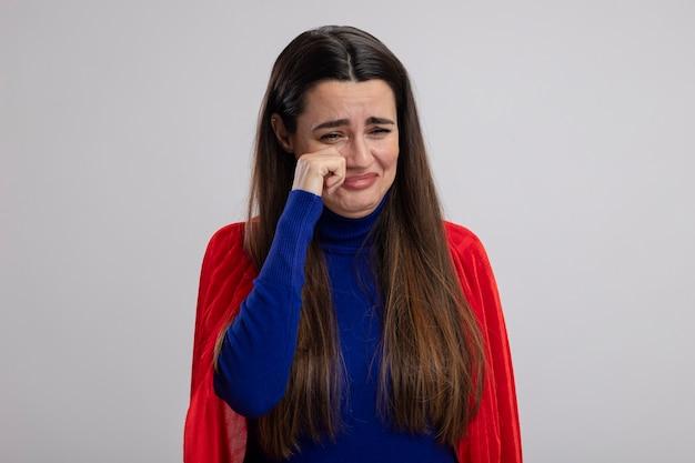 Плачет молодая девушка супергероя, вытирая глаза рукой, изолированной на белом