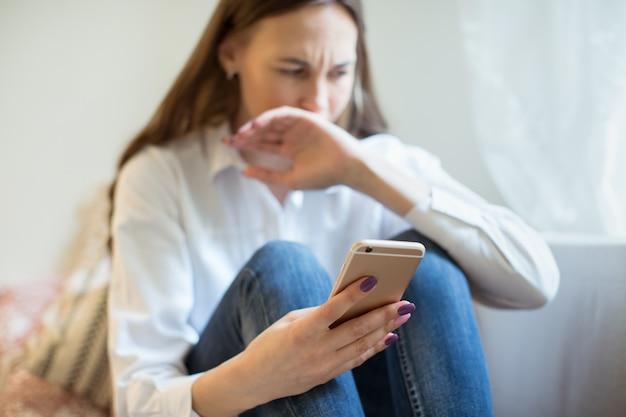 電話を見てうつ病で泣いている若い女性は、手で口を覆って、悪い知らせを得ます。悪いメッセージを受け取って心配している悲しい少女。否定的な感情