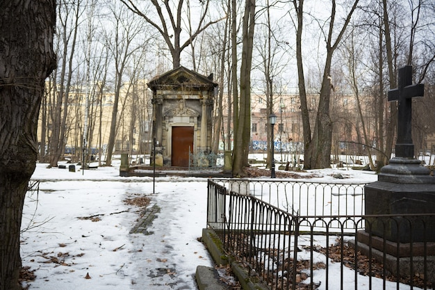 Crypt of horwitz family, large stone tomb among snow and bare trees in the distance and grave with black cross on the right - smolenskoe lutheran cemetery, russia, saint petersburg, march 2021