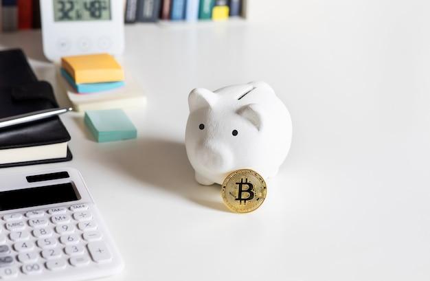 Криптовалюта, биткойн с копилкой на столе. финансы и технологии