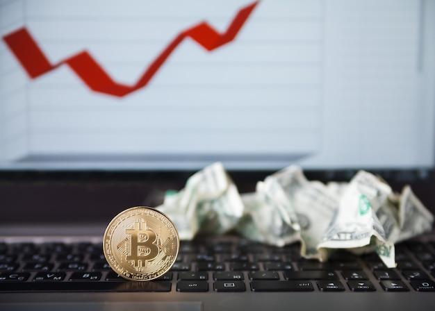 Криптовалюта. золотые монеты bitcoin и скомканные доллары на клавиатуре ноутбука