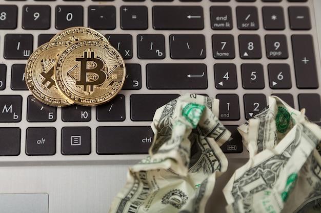Криптовалюта. золотые монеты биткойн и мятые доллары