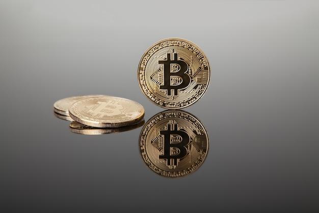 Криптовалюта. золотые биткойны на сером стекле с отражением